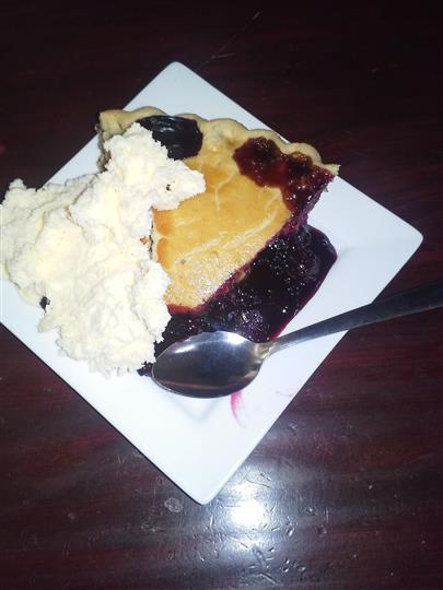 A piece of berrie-pie served with cream cheese