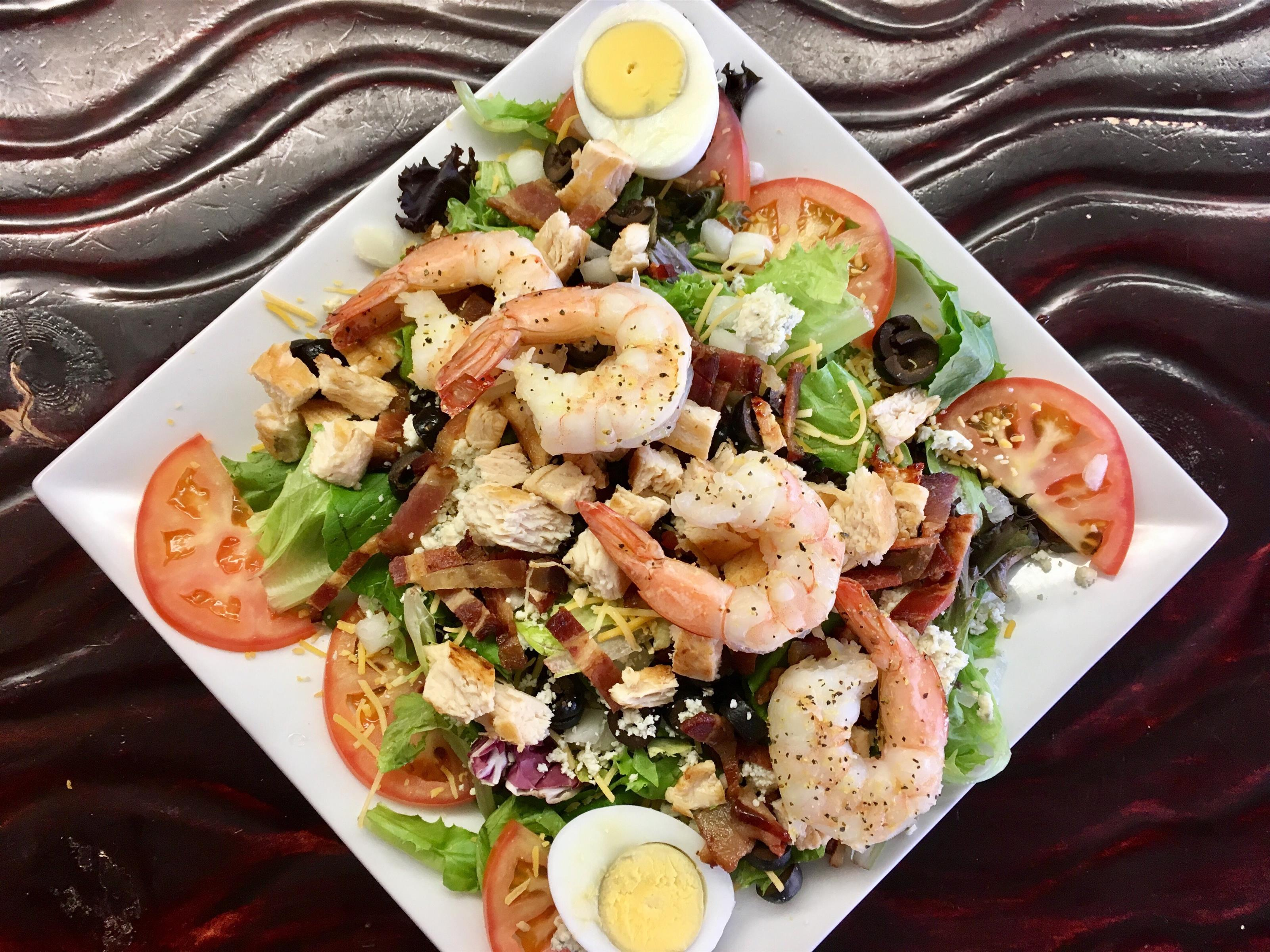 A fresh veggie salad topped with egg and shrimp