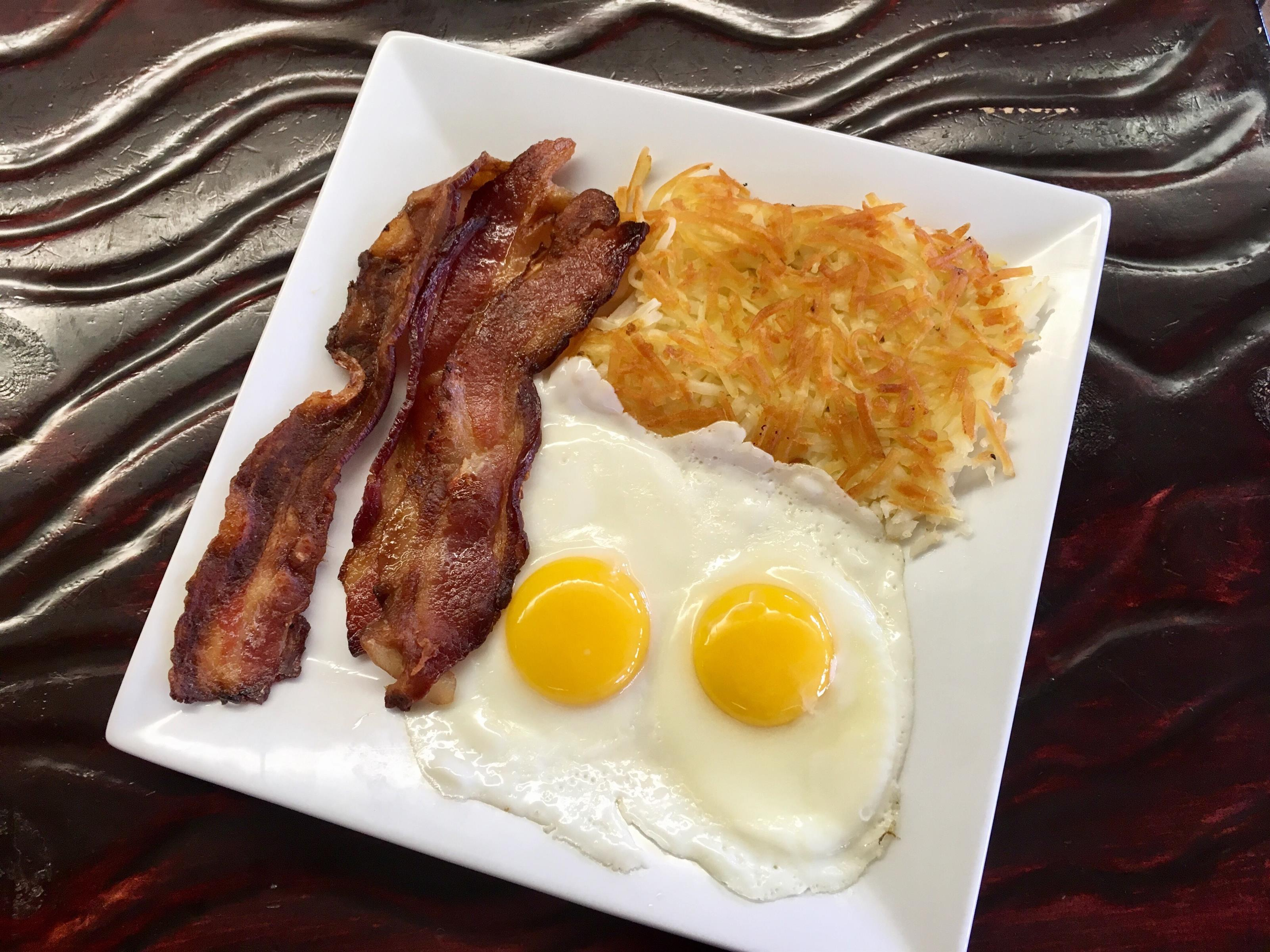 2 slices of bacon, 2 fried eggs and hashbrowns on a plate