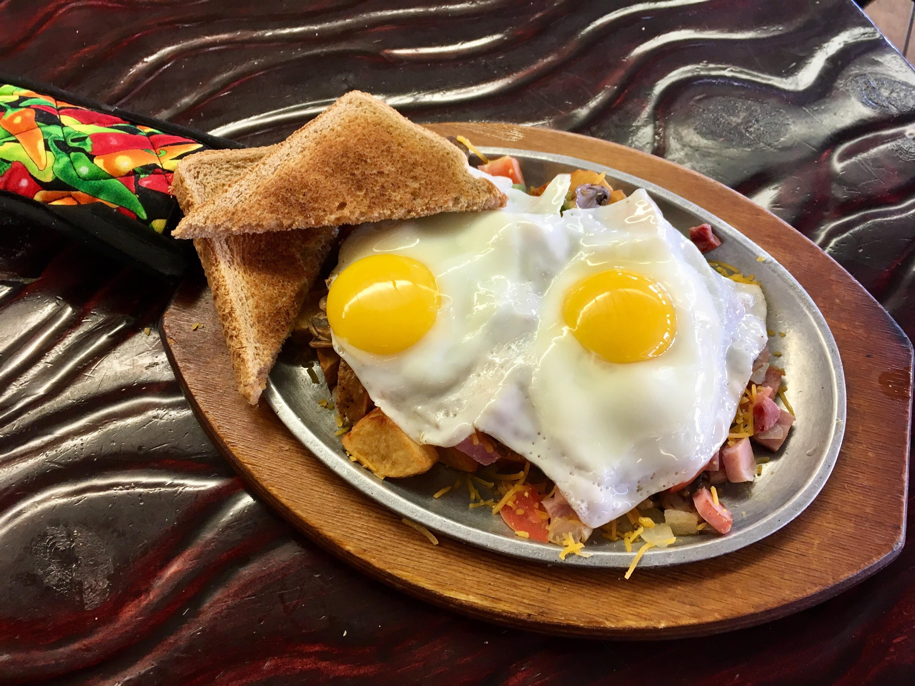 Two sunny side up eggs, served over fries, cheddar, slices of tomato and cubes of ham and bacon