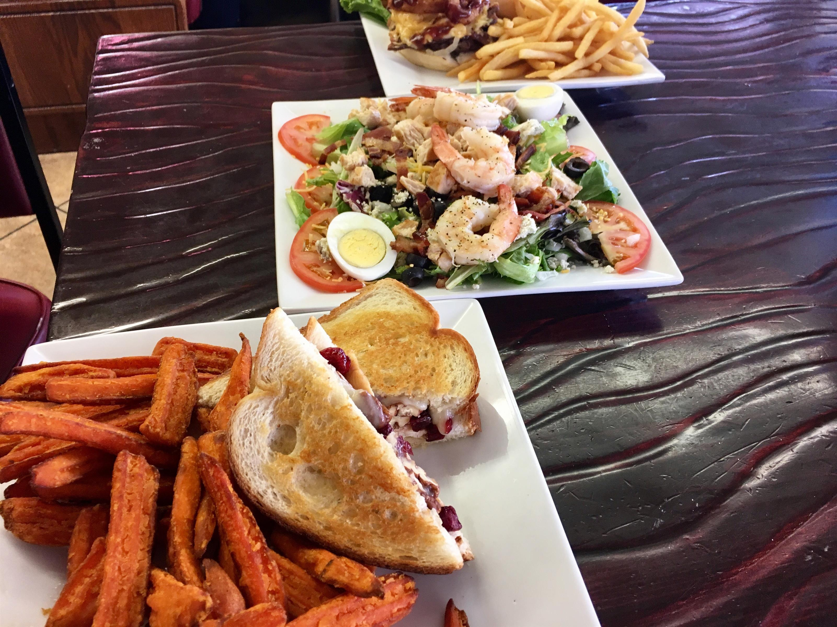 3 plates of food including a sandwich with sweet potato fries on 1 plate, a salad with shrimp, hard boiled eggs & tomatoes on top of lettuce on the 2nd place, and french fries with a sandwich on the 3rd plate