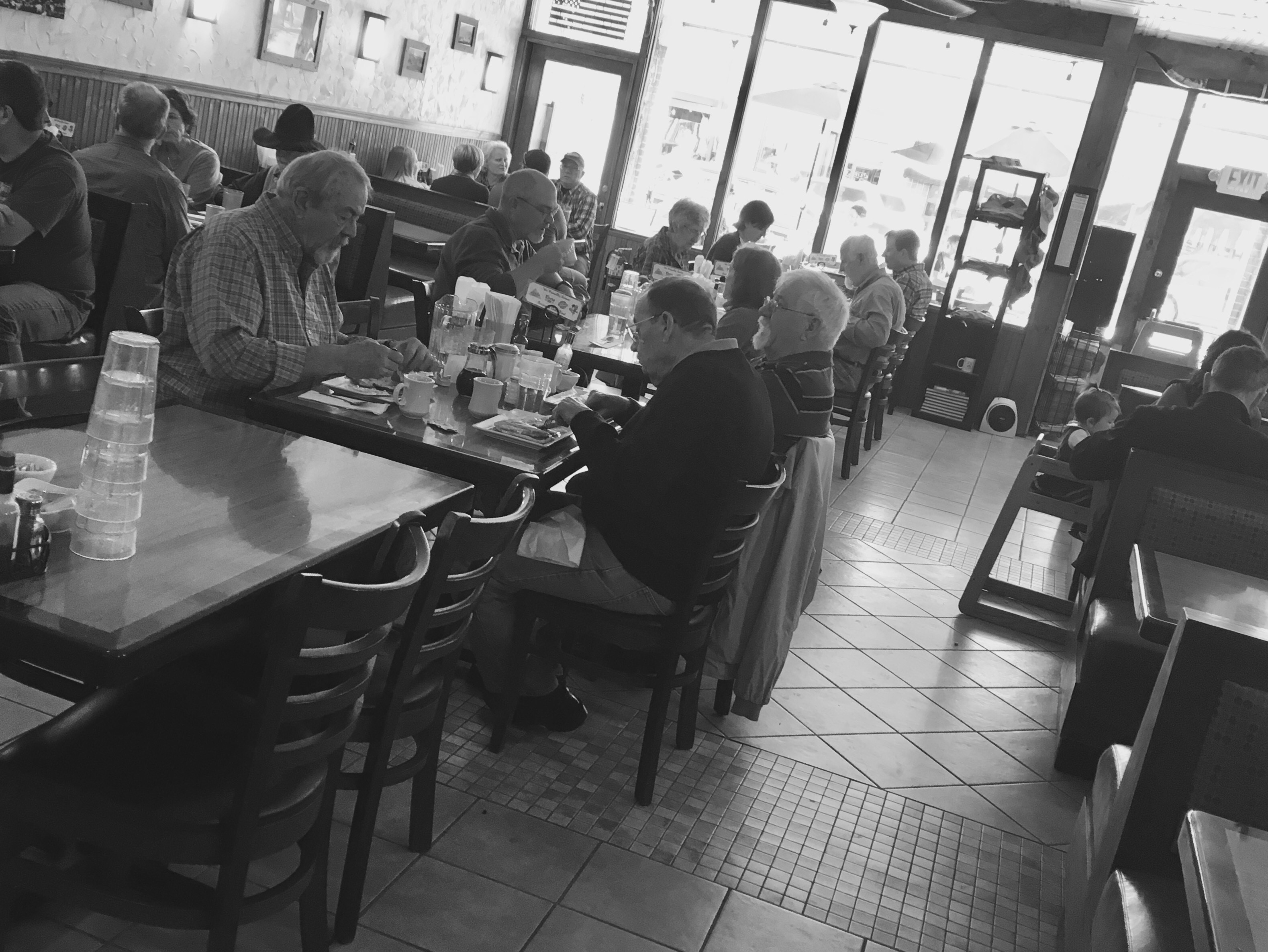 A black & white photo of people having breakfast in the restaurant