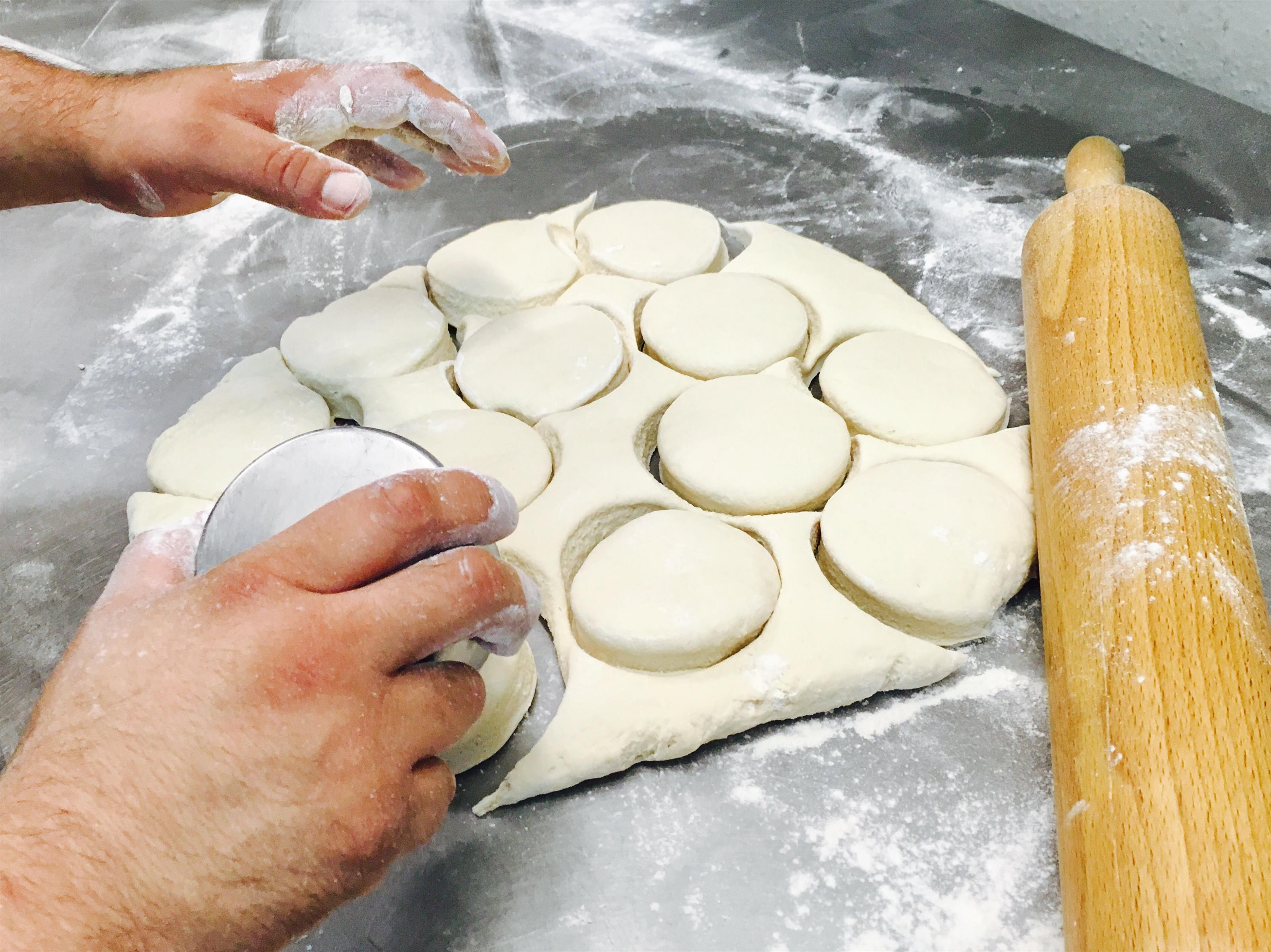 A chef cutting the dough with a cup