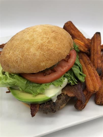 burger with bacon, avocado, cheese, lettuce, tomato and a side of fries