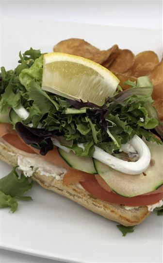 open face sandwich with tomato, cucumber, lettuce. side of potato chips