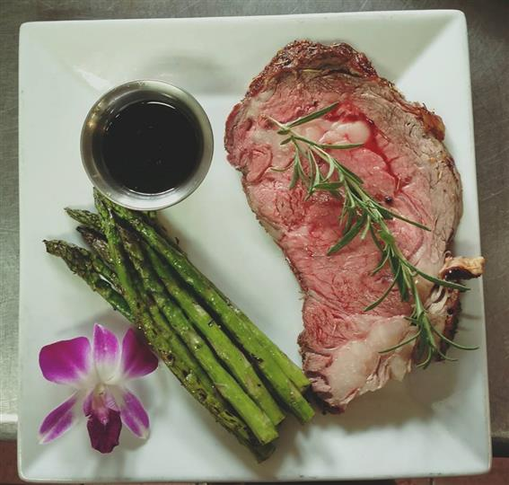 Steak with a side of asparagus and sauce