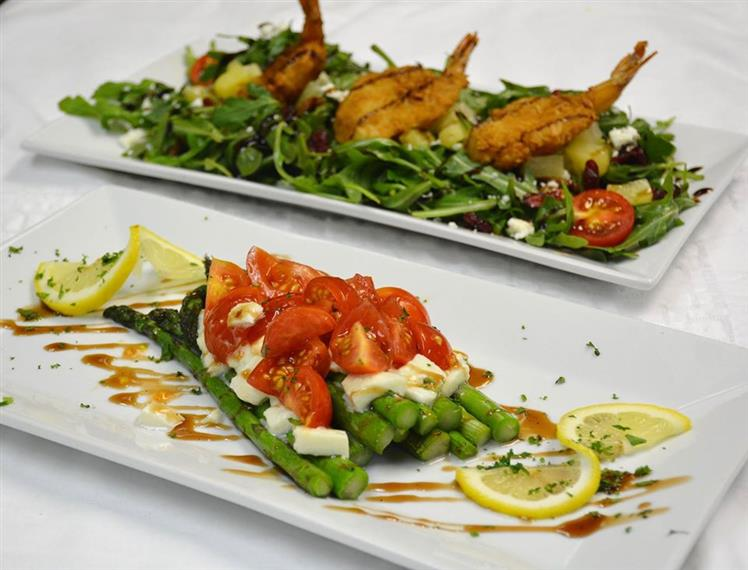 asparagus with mozzarella and tomatoes on top on one plate.  the 2nd plate has a salad with fried shrimp on top