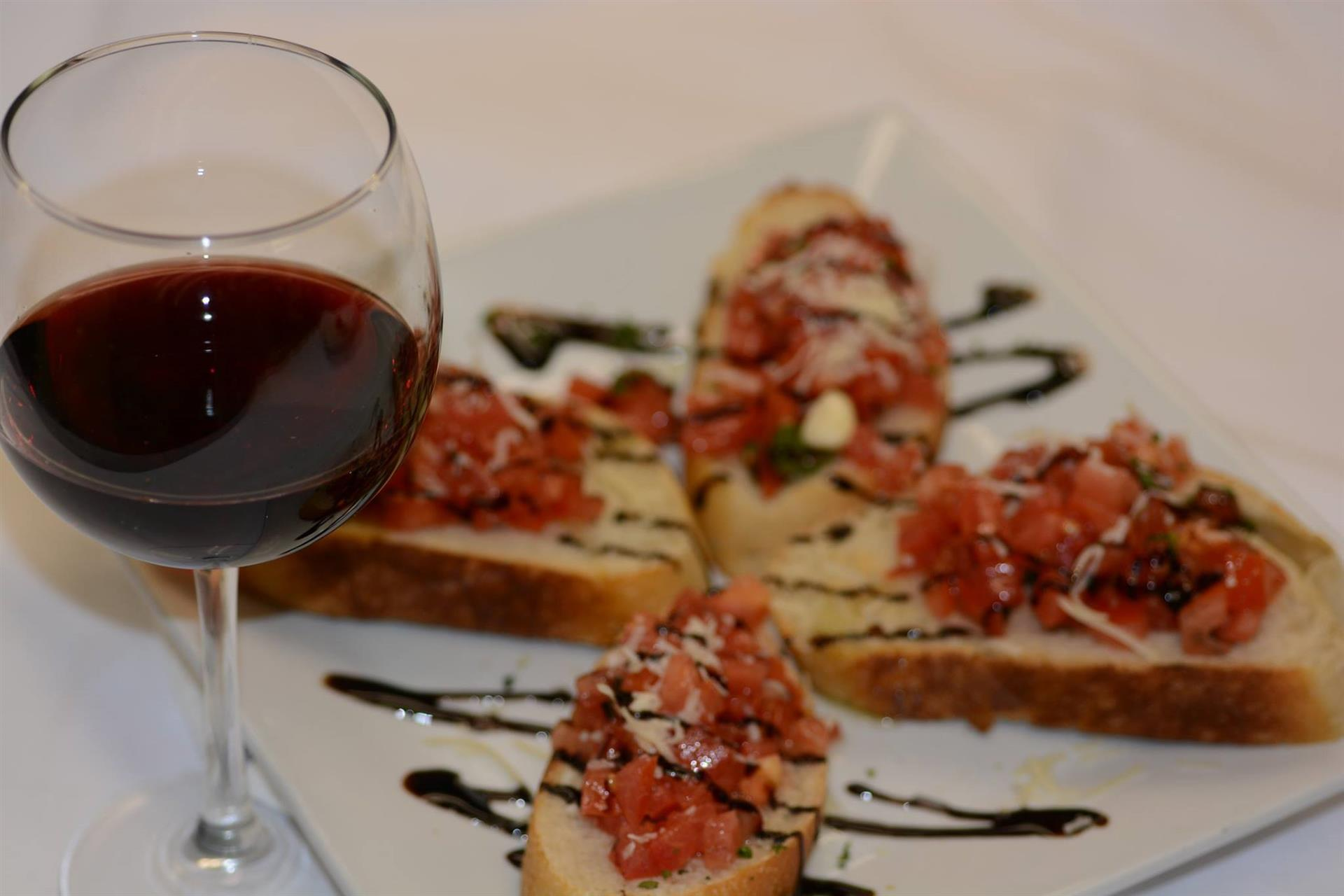 glass of red wine with bruschetta on a plate drizzled with balsamic glaze