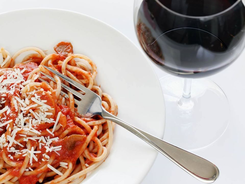 plate of spaghetti with red sauce and sprinkled parmesan cheese next to a glass of red wine