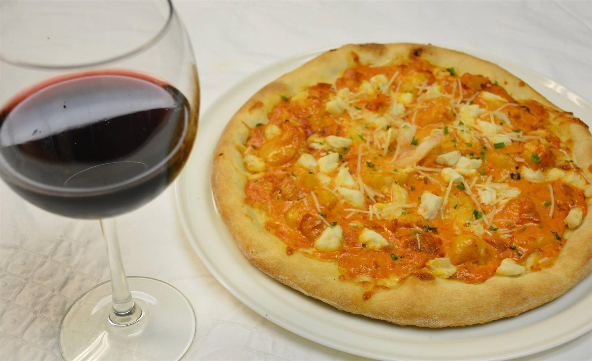 glass of red wine next to a plate with a shrimp scampi pizza