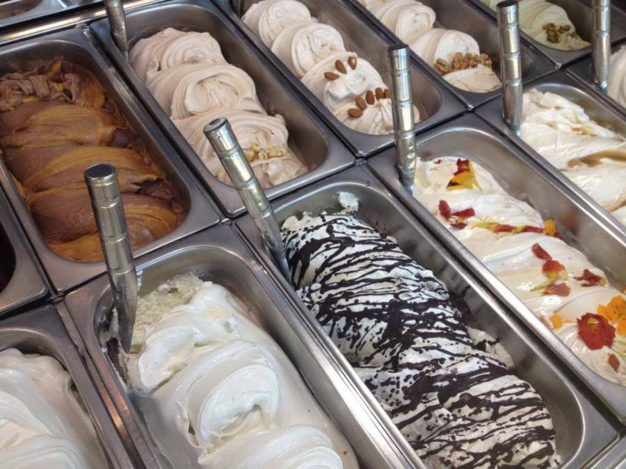 assortment of gelato in tubs with ice cream scoopers