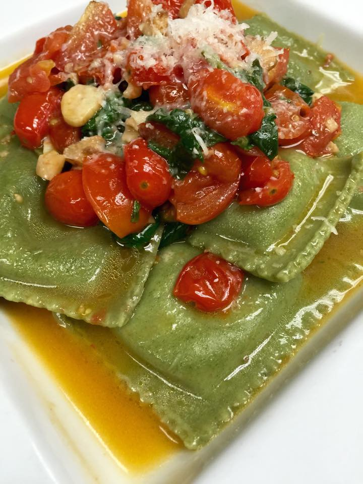 ravioli with tomatoes, spinach and cheese sprinkled on top