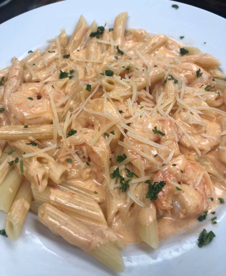 penne paste with shrimp and a sauce sprinkled with parmesan cheese
