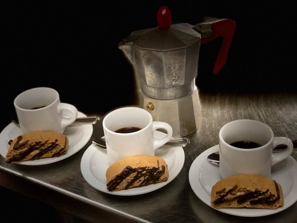 3 espresso mugs with espresso inside on saucers with a spoon and a biscotti drizzled with chocolate