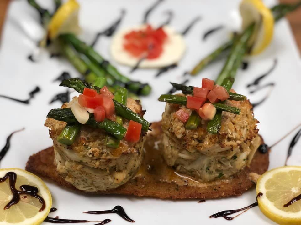 2 meatballs on a plate with asparagus and bruschetta, with lemon garnish drizzled with balsamic glaze