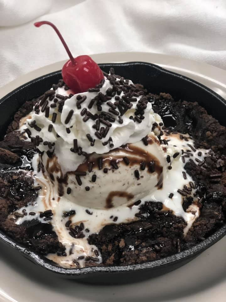 Cookies & Cream Icecream in a dish with chocolate syrup, whipped cream and a cherry on top