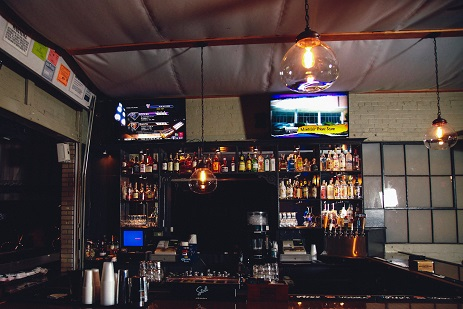 close-up view of behind the bar with two televisions