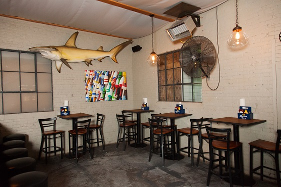 high-top tables with chairs and large fan on the wall with mounted shark