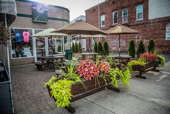 outside view of stella's with picnic tables covered with umbrellas and various flowers and plants