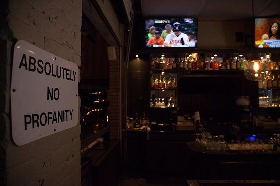 bar area with television and a sign that reads absolutely no profanity