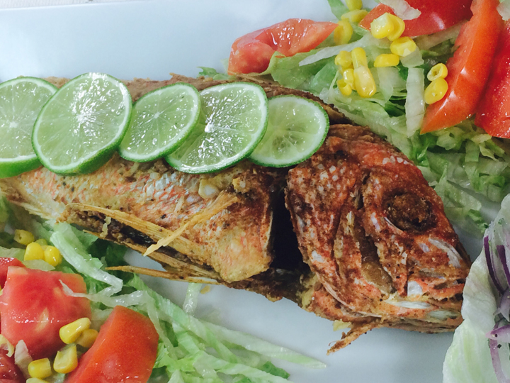 whole fried fish with lime wedges over a bed of lettuce