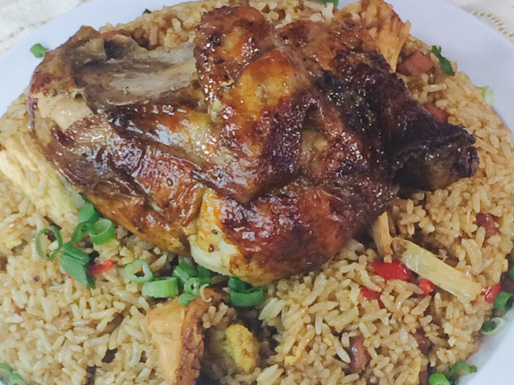 marinated half chicken over a bed of vegetable rice