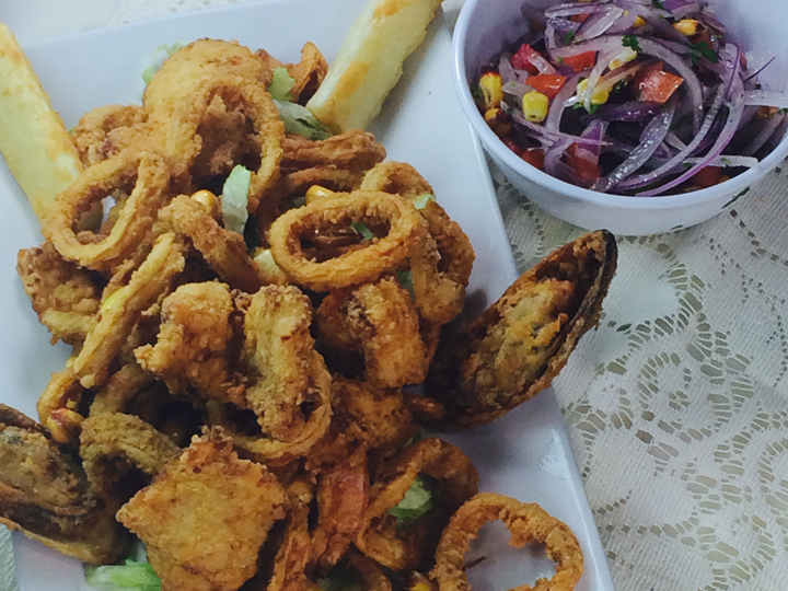 fried calamari on a plate with a side vegetables salad