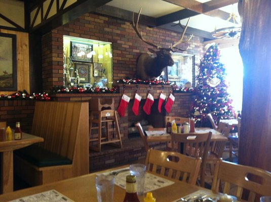 Inside of the restaurant with a christmas tree in the corner and five stockings hanging on the wall,