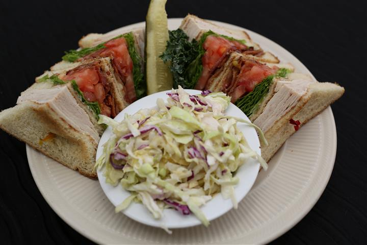 large double decker turkey club sandwich with a side bowl of coleslaw
