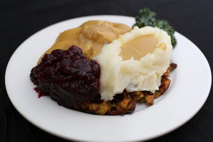 marinated chicken with mashed potatoes with gravy, cranberry sauce and vegetables