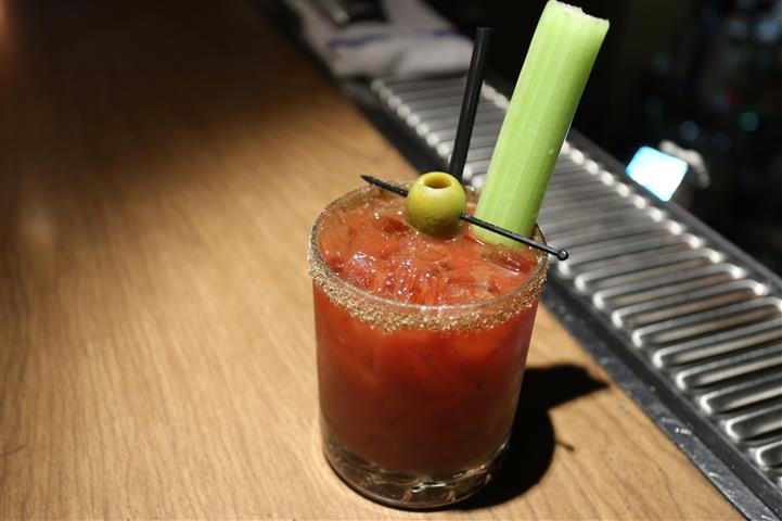 Bloody mary on ice with straw, celery, olive on bar counter