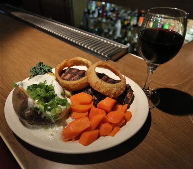 cooked steak topped with fried onion rings and a side of carrots with a baked stuffed potato all accompanied with a glass of wine