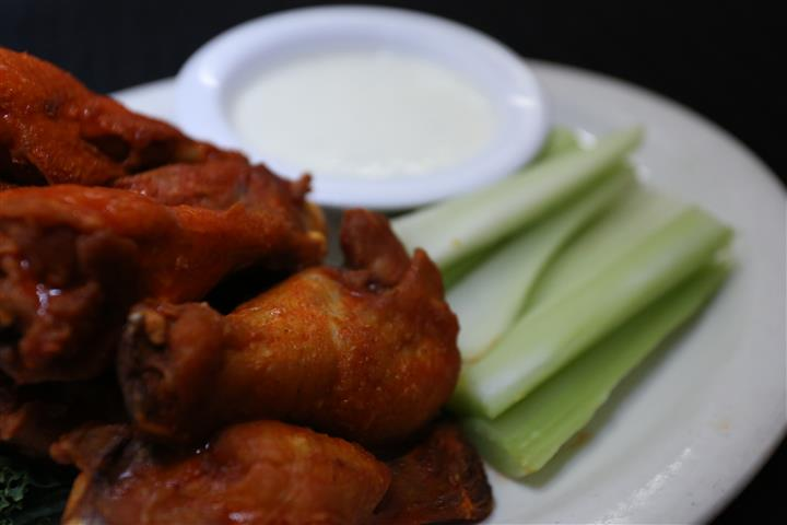 buffalo wings on a plate with celery sticks and dipping sauce in a bowl