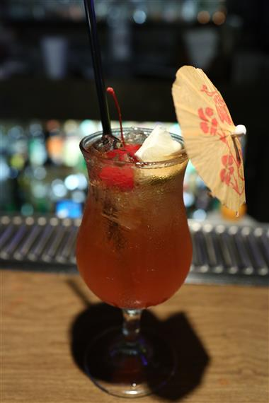 Mixed cocktail with lemon wedge, cherries, umbrella on bar top.