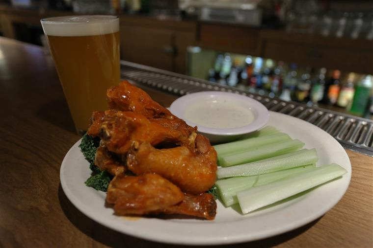 Chicken wings with celery and ranch dressing, full beer glass on side.