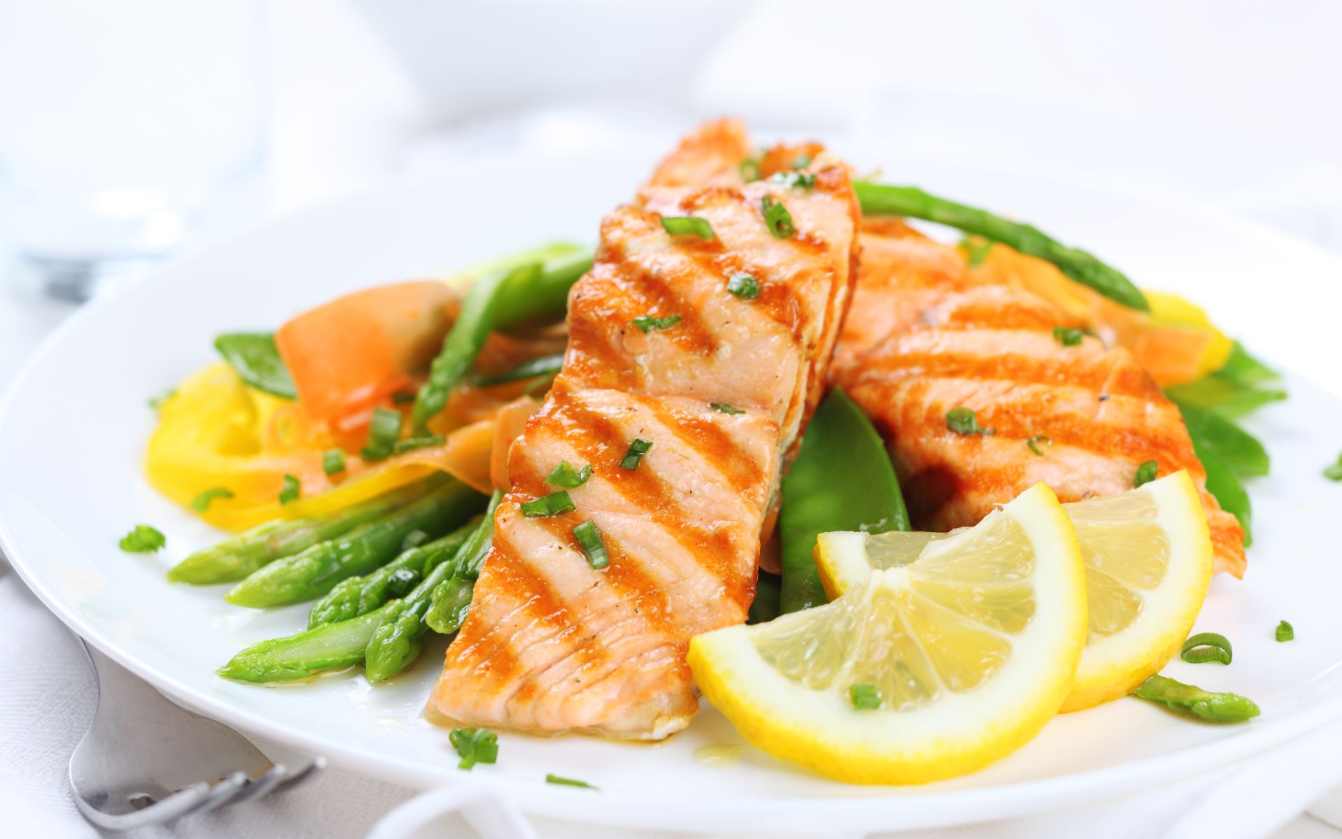 Salmon over asparagus and mixed veggies with lemon slices