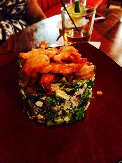 Fried shrimp and greens on table
