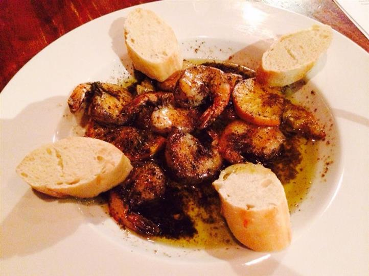 Plate of blackened shrimp with pieces of bread