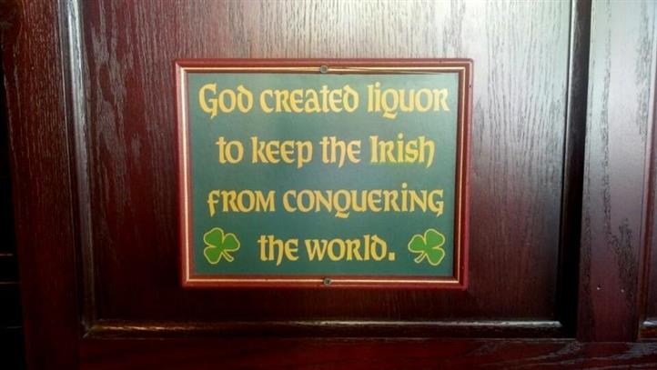 """A sign on the wall that says """"God created liquor to keep the Irish from conquering the world""""."""
