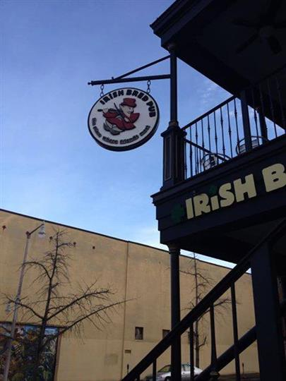 Our outdoor circular sign hanging from a pole that reads Irish Bred Pub, the place where friends meet with a cartoon-like man wearing a hat in the middle