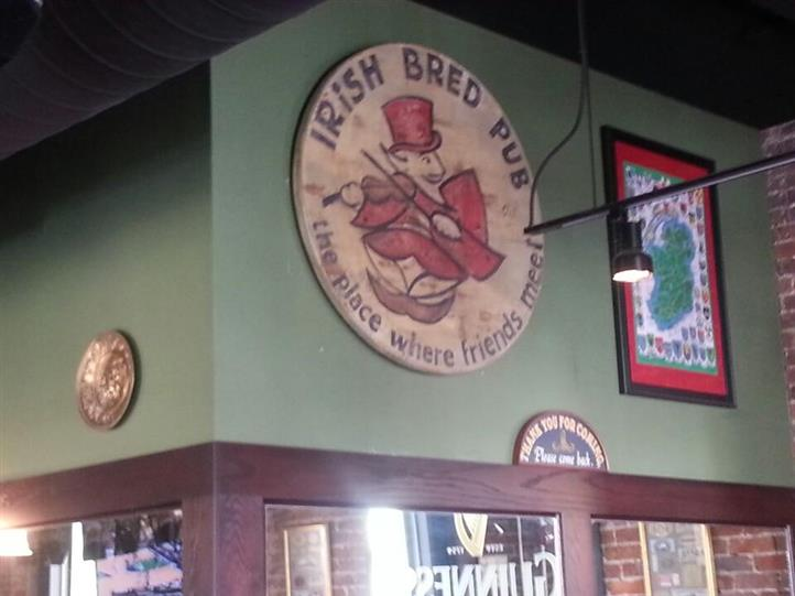 A circular sign hanging on the wall that reads Irish Bred Pub, the place where friends meet with a cartoon-like man in the middle wearing a hat.