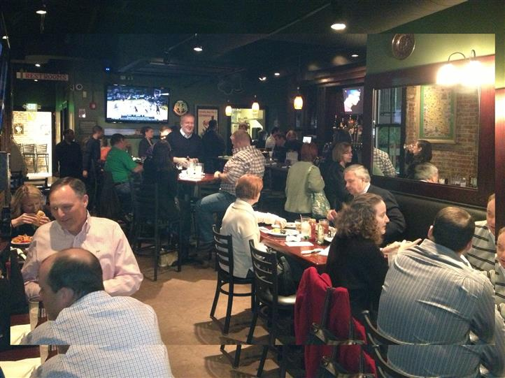 Indoor seating area with guests enjoying meals to a basketball game playing on a TV.