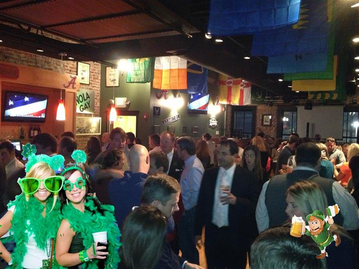 A crowded room with people talking to each other. Two shamrock decorated female guests holding beers.