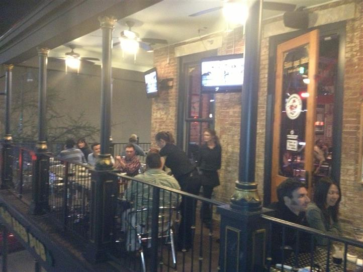 Outdoor seating in our 2nd story balcony with guests being served by our staff.