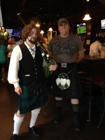 Two male costumed guests both wearing kilts and one carrying bagpipes.