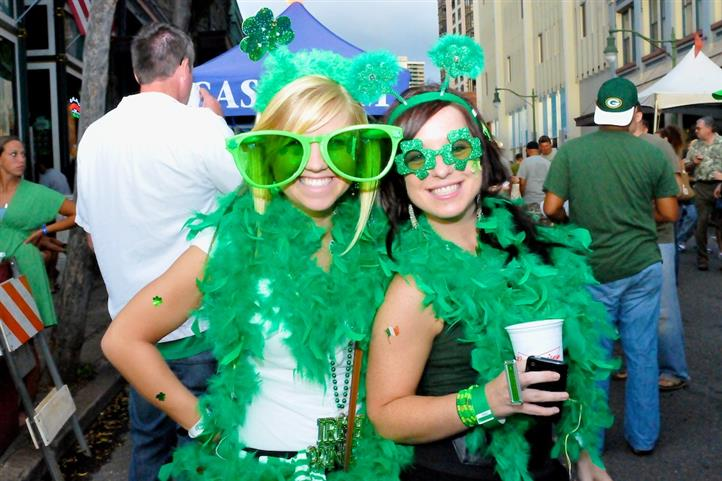 Two shamrock decorated female guests enjoying beer.