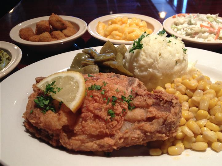 Fried fish topped with a slice of lemon, with corn, mashed potatoes, green beans, hush puppies, macaroni and cheese and slaw.