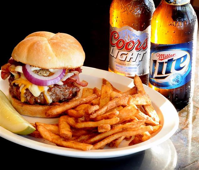 Cheeseburger with onions, fries, a pickle sitting next to a Coors Light and Miller Light Bottles of beer