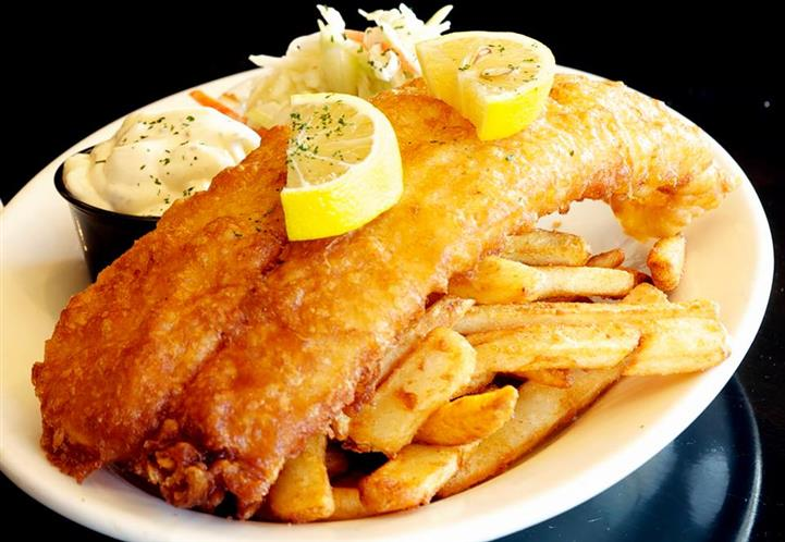Fish and chips. Topped with two lemon slices with sides of slaw and mashed potatoes