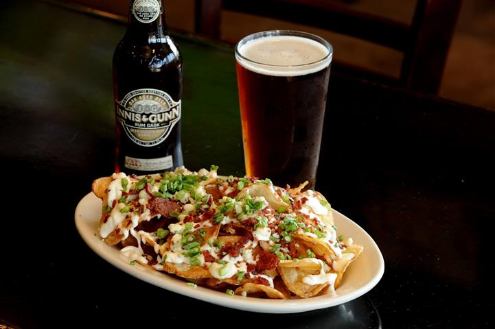 Potato chips covered in Bleu Cheese with bacon bits and scallions with a bottle and pint of beer